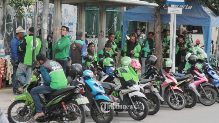 DAERAH KUMPUL OJOL - Sejumlah pengemudi ojol asyik bercengkerama sambil menunggu penumpang di Jalan Jati Baru Raya, Cideng, Jakarta Pusat, Rabu (8/4/2020). Mereka seperti tak memperdulikan larangan untuk kumpul bergerombol yang tertuang dalam aturan PSBB yang dikeluarkan oleh pemerintah, karena aksi mereka itu bisa menyebarkan wabah Covid-19. WARTA KOTA/NUR ICHSAN