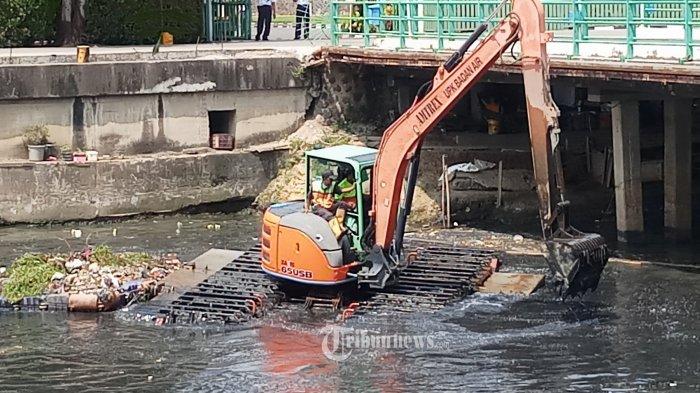 KERUK ENDAPAN LUMPUR - Petugas UPk Badan Air Dinas Lingkungan Hidup dibantu alat berat sedang mengeruk lumpur yang mengendap di Kali Mookervart, Jalan Daan Mogot Km 15, Jakarta Barat, Senin (26/4/2021). Pengerukan dilakukan mengingat di aliran kali ini banyak sekali endapan lumpur yang menumpuk bahkan hingga membentuk seperi daratan, yang menjadi salah satu penyebab banjir di ibukota. WARTA KOTA/NUR ICHSAN