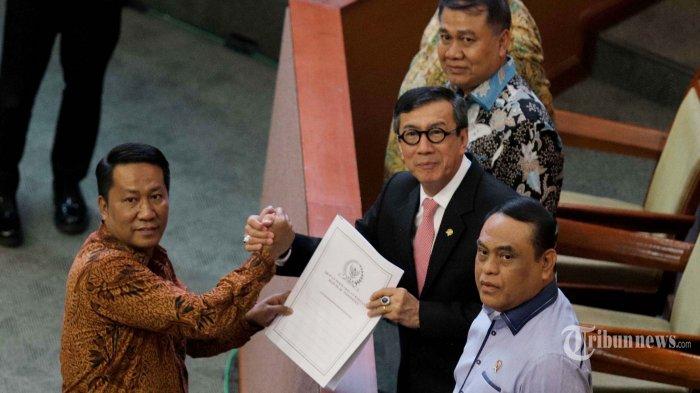 Menteri Hukum dan HAM Yasonna Laoly saat menyerahkan dokumen kepada Ketua Baleg Supratman Andi Agtas saat Rapat Paripurna DPR di Kompleks Parlemen, Senayan, Jakarta Pusat, Selasa (17/9/2019). Pemerintah dan DPR menyepakati pengesahan revisi Undang-Undang (UU) Nomor 30 Tahun 2002 tentang Komisi Pemberantasan Korupsi (KPK) yang dihadiri oleh 80 orang anggota DPR.