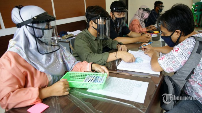 Petugas menggunakan penutup wajah (face shield) ketika memberikan layanan dokumen kependudukan kepada warga di Dinas Kependudukan dan Catatan Sipil Kecamatan Pamulang, Tangerang Selatan, Banten, Jumat (29/5/2020). Penggunaan face shield tersebut untuk mencegah penyebaran Covid-19 serta sebagai persiapan rencana penerapan 'New Normal'. TRIBUNNEWS/IRWAN RISMAWAN