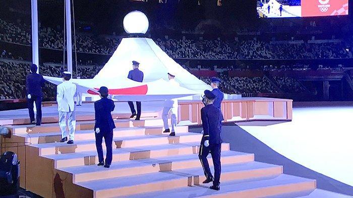 Bendera Jepang dikibarkan dengan latar belakang Gunung Fuji saat upacara Pembukaan Olimpiade Tokyo, Jumat (23/7/2021) malam.