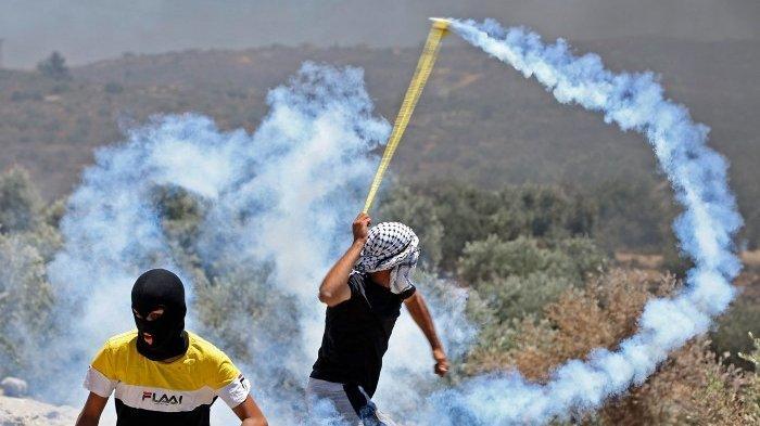 Seorang pengunjuk rasa Palestina bertopeng melemparkan kembali tabung gas air mata ke arah pasukan Israel selama bentrokan di kota Beita, dekat kota Nablus, Tepi Barat yang diduduki, di seberang pos pemukim liar Israel yang baru didirikan di Eviatar, pada 9 Juli 2021.