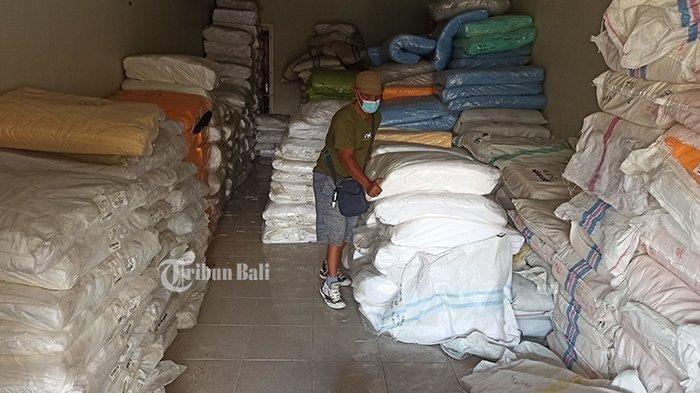 Pengusaha garmen Made Suparta menunjukkan tumpukan kain bahan kaus oleh-oleh khas Bali di gudangnya, kawasan Tukad Pancoran, Denpasar, Minggu 29 Agustus 2021. Kini dia beralih usaha kuliner.