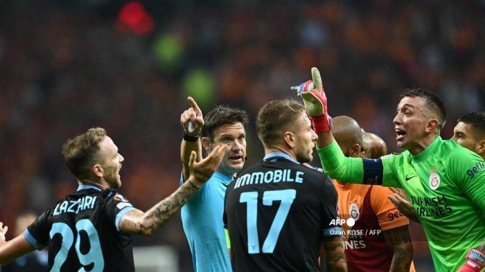 Penjaga gawang Galatasaray Fernando Muslera (kanan) menerima kartu kuning saat berdebat dengan wasit selama pertandingan sepak bola grup E Liga Eropa UEFA antara Galatasaray dan Lazio di Kompleks Olahraga Ali Sami Yen di Istanbul pada 16 September 2021.