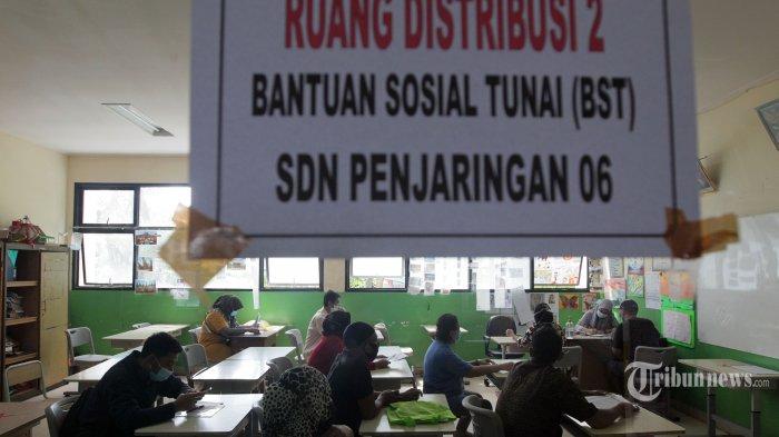 Warga saat mengantre untuk menerima Bantuan Sosial Tunai (BST) keluarga penerima manfaat di SDN Penjaringan 06, Jakarta Utara, Selasa (19/1/2021). Pemerintah menyalurkan BST untuk empat bulan kedepan sebesar Rp 300.000 per keluarga penerima manfaat yang diberikan langsung kepada warga melalui Bank DKI. Tribunnews/Jeprima