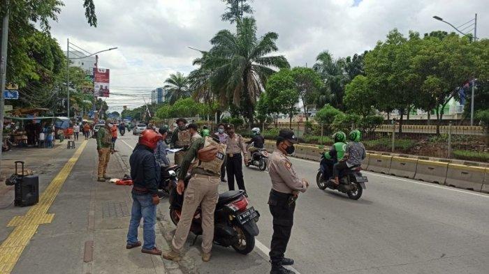 Polisi menyekat perbatasan Jakarta Utara dan Jakarta Pusat di Jalan Gunung Sahari, depan Maspion, Pademangan, Jakarta Utara, Jumat (18/12/2020).