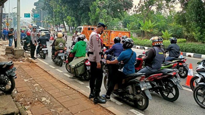 Para petugas kepolisian sedang melakukan pemeriksaan surat kepada para pengemudi yang melintas Jalan Lenteng Agung