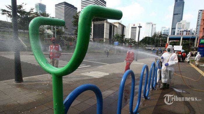 Petugas PMI Jakarta Pusat melakukan penyemprotan cairan disinfektan di kawasan Dukuh Atas, Jakarta, Minggu (31/5/2020). Penyemprotan di fasilitas umum tersebut untuk mencegah penyebaran Covid-19 serta terkait penerapan tatanan normal baru (new normal). TRIBUNNEWS/IRWAN RISMAWAN