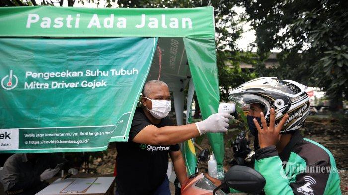 Petugas saat melakukan pengecekan suhu tubuh driver Gojek di Posko Aman J3K kawasan Pulomas, Jakarta Timur, Selasa (11/8/2020). Posko Aman J3K merupakan tempat melakukan penyemprotan disinfeksi kendaraan dan helm, pendistribusian masker, hairnet, dan hand sanitizer bagi para mitra driver. Tribunnews/Jeprima