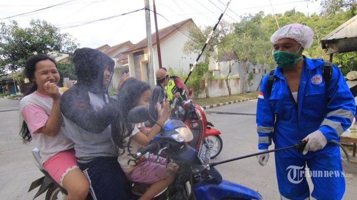 PENYEMPROTAN DISINFEKTAN - Sejumlah relawan menyemprot disinfektan pada warga dan pengendara bermotor yang masuk ke Perumahan Talangsari Regency RT 31 Kelurahan Tanah Merah Samarinda Utara, Kalimantan Timur. Minggu (29/3/2020). Upaya pencegahan menyebarnya wabah Virus Corona (Covid-19). (TribunKaltim/NEVRIANTO HARDI PRASETYO) *** Local Caption ***  dari