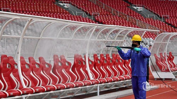 Seorang pekerja menyemprotkan desinfektan di dalam tanah stadion Gelora Bung Karno di Jakarta. Kamis (26/3/2020). Sebagai langkah untuk membantu menghentikan penyebaran virus corona COVID-19. (AFP/ADEK BERRY)