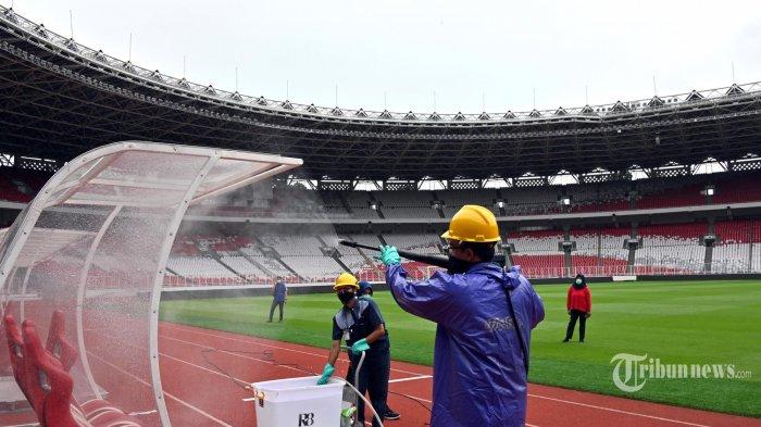 Para pekerja menyemprotkan desinfektan di dalam Area Stadion Gelora Bung Karno (GBK) di Jakarta. Kamis (26/3/2020). Sebagai langkah untuk membantu menghentikan penyebaran virus corona COVID-19. (AFP/ADEK BERRY)