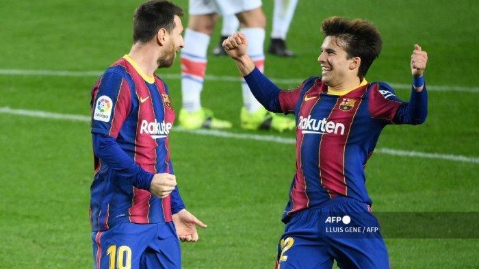 Penyerang Barcelona asal Argentina Lionel Messi merayakan dengan gelandang Spanyol Barcelona Riqui Puig (kanan) setelah mencetak gol selama pertandingan sepak bola Liga Spanyol antara FC Barcelona dan Deportivo Alaves di stadion Camp Nou di Barcelona pada 13 Februari 2021. LLUIS GENE / AFP