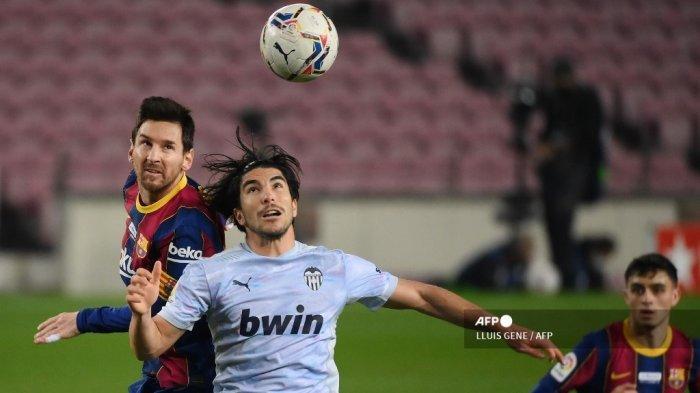 Penyerang Barcelona asal Argentina Lionel Messi (kiri) bersaing dengan gelandang Spanyol Valencia Carlos Soler selama pertandingan sepak bola liga Spanyol antara FC Barcelona dan Valencia CF di stadion Camp Nou di Barcelona pada 19 Desember 2020. LLUIS GENE / AFP