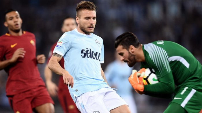 Penyerang Lazio, Ciro Immobile (tengah), melihat bola berhasil ditangkap kiper AS Roma, Alisson Ramses (kanan), dalam pertandingan Liga Italia 2017-2018 di Stadio Olimpico, Roma, Italia, pada Minggu (15/4/2018).