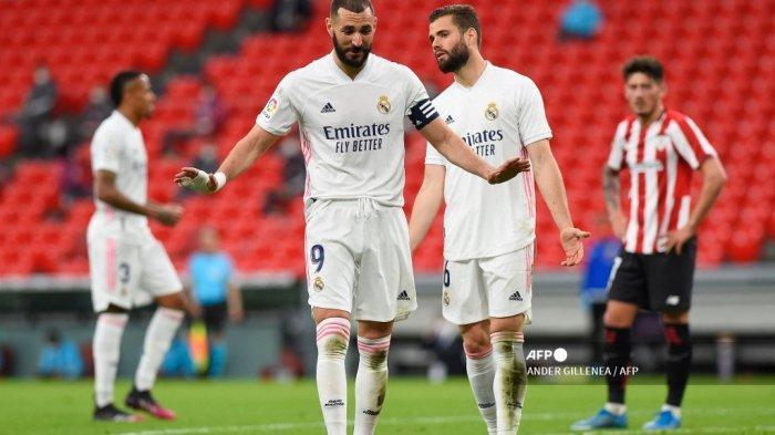 Penyerang Prancis Real Madrid Karim Benzema dan gerakan bek Spanyol Real Madrid Nacho Fernandez (kanan) selama pertandingan sepak bola Liga Spanyol antara Athletic Club Bilbao dan Real Madrid CF di stadion San Mames di Bilbao pada 16 Mei 2021. ANDER GILLENEA / AFP