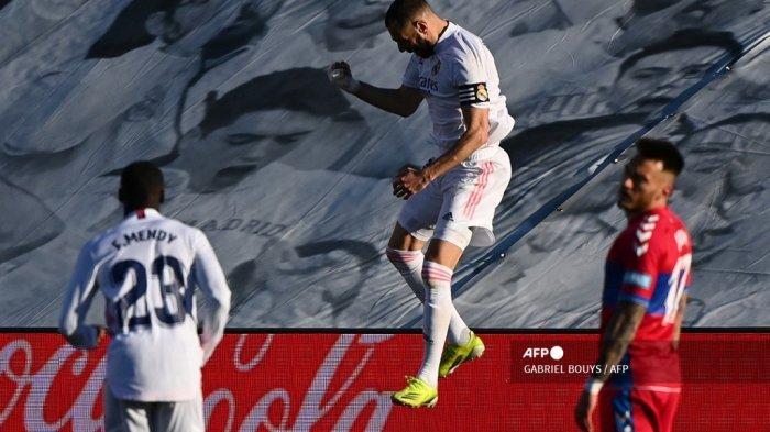 Penyerang Prancis Real Madrid Karim Benzema (tengah) melakukan selebrasi setelah mencetak gol dalam pertandingan sepak bola Liga Spanyol antara Real Madrid dan Elche di stadion Alfredo Di Stefano di Valdebebas, timur laut Madrid, pada 13 Maret 2021. GABRIEL BOUYS / AFP