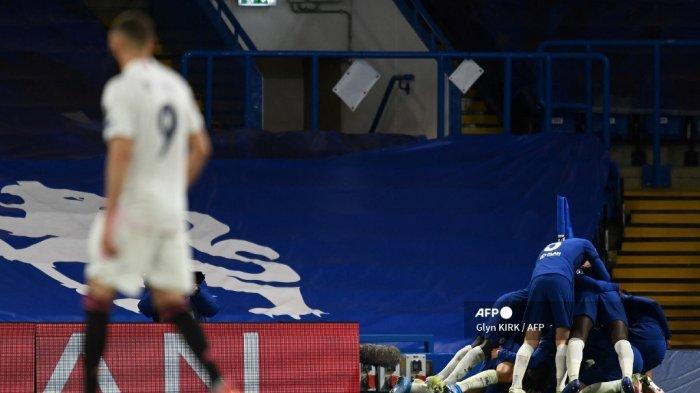 Penyerang Real Madrid asal Prancis Karim Benzema (kiri) bereaksi ketika gelandang Inggris Chelsea, Mason Mount dikerumuni rekan satu timnya setelah mencetak gol kedua dalam pertandingan sepak bola semifinal leg kedua Liga Champions UEFA antara Chelsea dan Real Madrid di Stamford Bridge di London pada 5 Mei. , 2021. Glyn KIRK / AFP