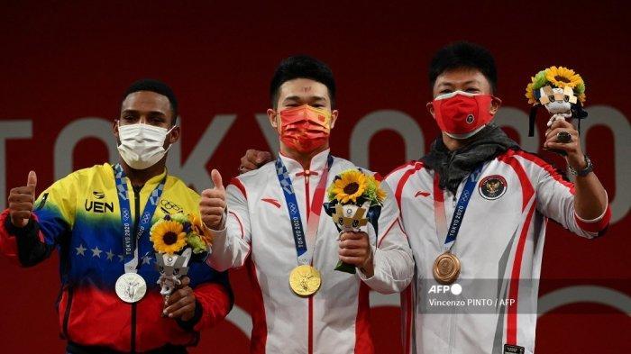 Peraih medali perak dari Venezuela Julio Ruben Mayora Pernia, peraih medali emas Shi Zhiyong dari China dan peraih medali perunggu dari Indonesia Rahmat Erwin Abdullah berdiri di podium untuk upacara kemenangan kompetisi angkat besi 73kg putra selama Olimpiade Tokyo 2020 di Tokyo International Forum di Tokyo pada 28 Juli 2021.