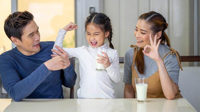 Ilustrasi anak yang minum susu bersama orang tuanya. Peran orang tua sangat penting agar Si Kecil rutin minum susu anak.