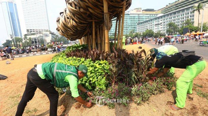 Petugas Suku Dinas Kehutanan Jakarta Pusat mengganti tanaman yang rusak di sekitar instalasi bambu Getah Getih, Jakarta, Minggu (23/6/2019). Perbaikan tersebut dilakukan karena tanaman hias di kawasan tersebut rusak akibat terinjak warga saat menghadiri perayaan HUT Jakarta ke-492, Sabtu (22/6). TRIBUNNEWS/IRWAN RISMAWAN