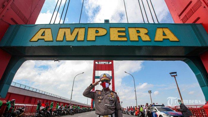 Kasat Lantas Polrestabes Palembang, AKBP Yusantyo Sandhy memimpin penghormatan bendera yang diikuti oleh sejumlah driver ojek online dan komunitas motor melakukan hormat bendera merah putih pada acara penghormatan detik-detik proklamasi pada hari Kemerdekaan Republik Indonesia ke 75 di Kawasan Jembatan Ampera, Palembang, Senin (17/8/2020). Pada acara penghormatan bendera detik-detik proklamasi diikuti oleh komunitas motor dan driver ojek online. TRIBUN SUMSEL/ABRIANSYAH LIBERTO