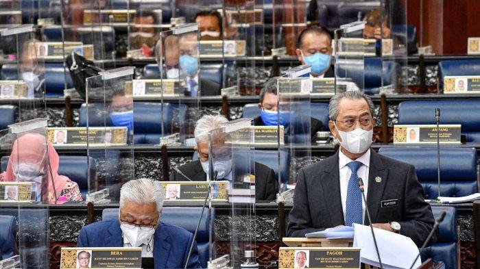 Foto selebaran dari Departemen Informasi Malaysia ini diambil dan dirilis pada 26 Juli 2021 menunjukkan Perdana Menteri Muhyiddin Yassin menyampaikan pidatonya selama sesi khusus Dewan Rakyat (Dewan Perwakilan Rakyat) di Parlemen di Kuala Lumpur, bersidang untuk pertama kalinya sejak Januari setelah ditangguhkan di bawah darurat virus corona.