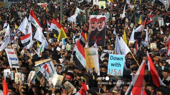 Demonstran Irak mengangkat bendera dan plakat ketika mereka berunjuk rasa di alun-alun Tahrir di ibu kota Baghdad pada 3 Januari 2021, untuk menandai satu tahun setelah serangan pesawat tak berawak AS menewaskan komandan terhormat Iran Qasem Soleimani dan letnan Iraknya Abu Mahdi al-Muhandis di dekat ibu kota. Ribuan pelayat Irak meneriakkan