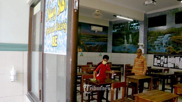 PERSIAPAN SEKOLAH HADAPI NEW NORMAL - Kepala Sekolah SMP Islam PAPB Semarang Drs. H Ramelan sedang melakukan pengecekan kesiapan sekolah untuk mempersiapkan kegiatan belajar mengajar 2020/2021 yang rencananya akan dimulai pada bulan Juli 2020 dengan menerapkan protokol pelaksanaan pencegahan Covid-19, Rabu (03/06/20). Persiapan kegiatan belajar mengajar sesuai dengan anjuran pemerintah dengan menerapkan aturan satu meja atau satu bangku hanya boleh diduduki satu peserta didik, sekolah wajib menyediakan hand sanitizer dan disinfektan tempat cuci tangan dan sabun disediakan di depan kelas, semua siswa dan guru yang ada di lingkungan sekolah wajib menggunakan masker, sekolah menyediakan termometer untuk mengecek suhu peserta didik dan setiap siswa sekolah diwajibkan mencuci tangan pakai sabun setelah melakukan kegiatan. (Tribun Jateng/Hermawan Handaka)