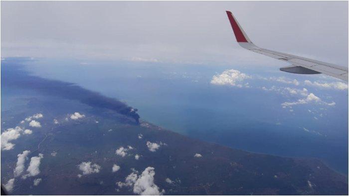 KEBAKARAN KILANG BALONGAN- Asap hitam membumbung di atas area kilang minyak Pertamina Balongan, Indramayu, Jawa Barat, terlihat dari kabin penumpang pesawat Batik Air ketika melintas di pesisir utara Pulau Jawa dalam penerbangan dari Bandara Soekarno-Hatta Tangerang menuju Bandara Adisoemarmo, Solo, Senin (29/3/2021), sekira pukul 12.34 WIB.