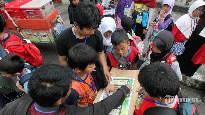 SAFARI RAMADAN - Sejumlah peserta Pesantren Kilat Safari Ramadan melihat peta saat menelusuri bangunan bersejarah di Jalan Cikapundung, Kota Bandung, Minggu (11/6/2017). Kegiatan yang diselenggarakan Pembinaan Anak-anak Salman (PAS) ITB itu, diikuti 60 siswa sekolah dasar dari berbagai kota di Jawa Barat yang akan berlangsung selama lima hari dengan materi pembelajaran yang diberikan pendidikan agama Islam, sejarah, arsitektur, dan ilmuan. (TRIBUN JABAR/GANI KURNIAWAN)