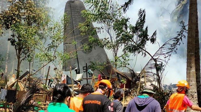 Dalam foto selebaran yang diambil pada tanggal 4 Juli 2021 dan diterima dari Satuan Tugas Gabungan Militer Filipina-Sulu (JTF-Sulu), petugas penyelamat tiba saat asap mengepul dari puing-puing pesawat angkut C-130 Angkatan Udara Filipina setelah jatuh di dekat bandara di kota Jolo, provinsi Sulu, dekat pulau selatan Mindanao.