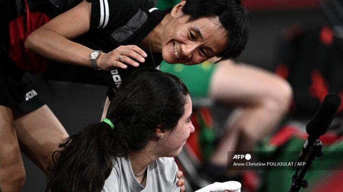 Petenis Suriah Hend Zaza (BOTTOM) dihibur oleh Liu Jia dari Austria setelah dikalahkan 4-0 dalam pertandingan tenis meja babak penyisihan tunggal putri mereka di Tokyo Metropolitan Gymnasium selama Olimpiade Tokyo 2020 di Tokyo pada 24 Juli 2021.