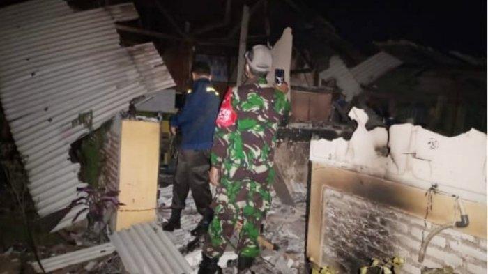 Petugas berjaga di bangunan tempat mengaji yang dibakar massa di Cilawu, Garut. Pembakaran dilakukan karena warga kesal guru mengaji tersebut mencabuli santri.