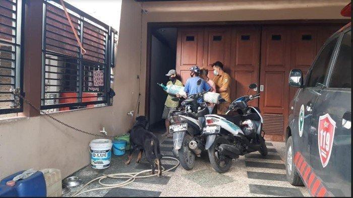 Petugas dari Dinkes Sumsel dibantu tukang bangunan tampak membawa tabung oksigen masuk ke dalam rumah Heriyanti anak Akidi Tio, Selasa (3/8/2021).