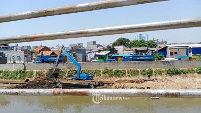 Alat berat sedang mengakat lumpur yang di angkat  dari dasar Kali Ciliwung, Kampung Pulo, Jakarta Pusat, Rabu(26/8/2020). Pengerukan kali masih terus dilakukan untuk melancarkan arus air agar tidak menimbulkan banjir  pada musim hujan. WARTA KOTA/HENRY LOPULALAN
