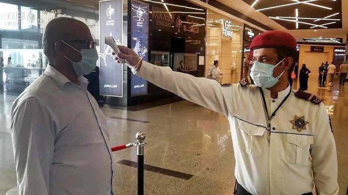 Petugas keamanan memeriksa suhu tubuh seorang pria sebelum berbelanja di supermarket di Riyadh, Arab Saudi, Senin (4/5/2020)