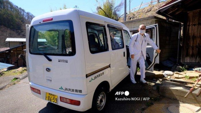 Petugas kesehatan tiba di rumah Kakino Yamaguchi, seorang wanita tua yang akan disuntik dengan vaksin virus corona Pfizer-BioNTech Covid-19, di desa Kitaaiki di Prefektur Nagano pada 21 April 2021.
