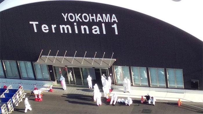 Petugas medis yang menangani wabah virus corona di kapal pesiar Diamond Princess kelelahan, Jumat (21/2/2020) dan duduk-duduk di tepi hangar Pelabuhan Yokohama.