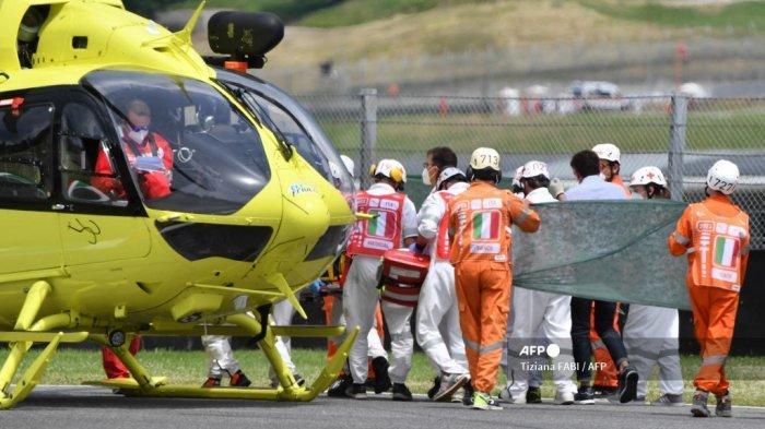 Petugas medis mengevakuasi pebalap Swiss Moto3 Jason Dupasquier dengan helikopter setelah mengalami kecelakaan saat sesi kualifikasi menjelang Grand Prix Moto GP Italia di trek balap Mugello di Scarperia e San Piero pada 29 Mei 2021. Pembalap Moto3 Swiss Jason Dupasquier dibawa ke rumah sakit setelah kecelakaan tiga sepeda yang menghentikan kualifikasi untuk Grand Prix sepeda motor Italia di Mugello pada 29 Mei 2021. Penyelenggara mengatakan remaja yang terserang itu sedang