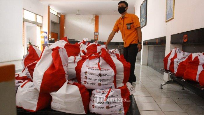 Petugas sedang merapikan bantuan pemerintah untuk warga yang terdampak Pandemi Covid-19 di Kantor Pos Pemuda, Jakarta Timur, Selasa (21/4/2020). Untuk pendistribusian wilayah DKI Jakarta, Pos Indonesia mengerahkan 4.640 karyawan yang ditugaskan untuk melakukan pengantaran dan tenaga administrasi pada lokasi drop point (RW), 240 kendaraan/truk dan 1.500 motor antaran. Seluruh Keluarga Penerima Manfaat (KPM) tinggal menunggu petugas pengantar Pos Indonesia di rumah masing-masing. Warta Kota/Angga Bhagya Nugraha