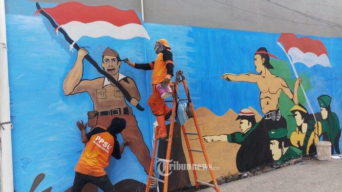 SAMBUT HUT RI KE-75 - Salbini dan Sugandi, petugas PPSU Kelurahan Krendang, Kecamatan Tambora, Jakarta Barat, sedang membuat lukisan dinding bertema kemerdekaan dalam rangka memeriahkan perayaan HUT RI ke-75, Jumat (7/8/2020). Lewat lukisan yang dibuatnya ini mereka mengajak masyarakat untuk mencintai tanah air Indonesia yang ber Bhinneka Tunggal Ika dalam bingkai NKRI, serta menghormati jasa para pahlawan yang telah berjasa merebut kemerdekaan Indonesia dari tangan penjajah. WARTA KOTA/NUR ICHSAN