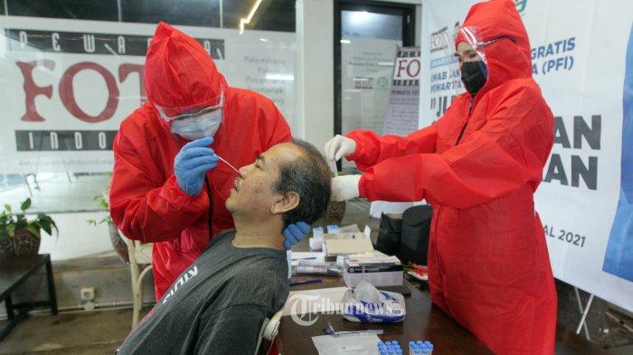 Petugas tenaga kesehatan saat mengambil sampel tes usap antigen COVID-19 dari wartawan foto di Sekretariat Pewarta Foto Indonesia (PFI) Pusat di kawasan Ampera, Jakarta Selatan, Minggu (14/2/2021).