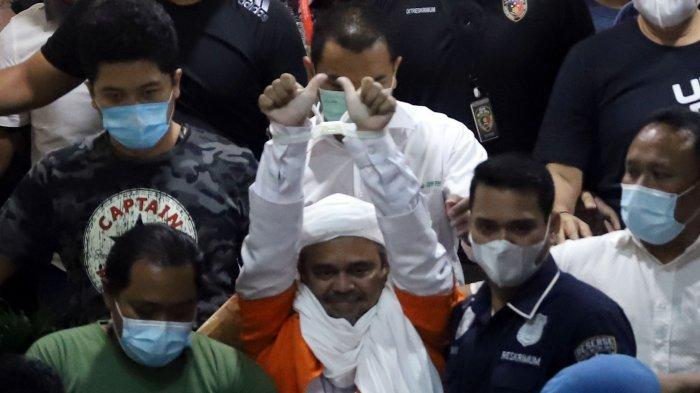 Pimpinan FPI Muhammad Rizieq Shihab menuju mobil tahanan setelah menjalani pemeriksaan di Polda Metro Jaya, Minggu (13/12/2020). Rizieq Shihab diperiksa sebagai tersangka kasus kerumunan di Petamburan.