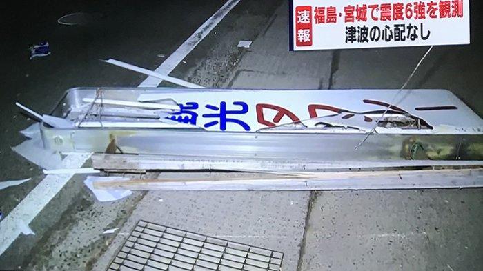 Plang kantor taksi Fukushima jatuh ke jalan raya saat gempa bumi, Sabtu (13/2/2021) malam.