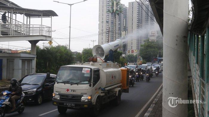 Relawan PMI Jakarta Barat melakukan penyemprotan cairan disinfektan di sepanjang Jalan Daan Mogot, Jakarta Barat, Senin (13/4/.2020), untuk memutus mata rantai penyebaran wabah Covid-19. (Warta kota/Nur Ichsan)