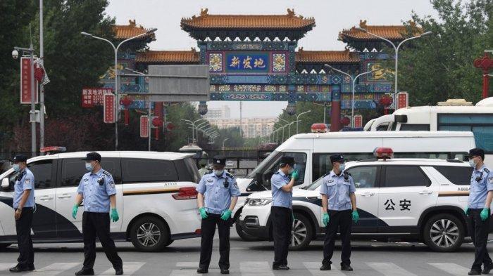 Polisi Cina menjaga pintu masuk ke pasar Xinfadi yang ditutup di Beijing pada 13 Juni 2020. Sebelas perumahan di Beijing selatan telah dikunci karena sekelompok kasus virus korona yang terkait dengan pasar daging Xinfadi