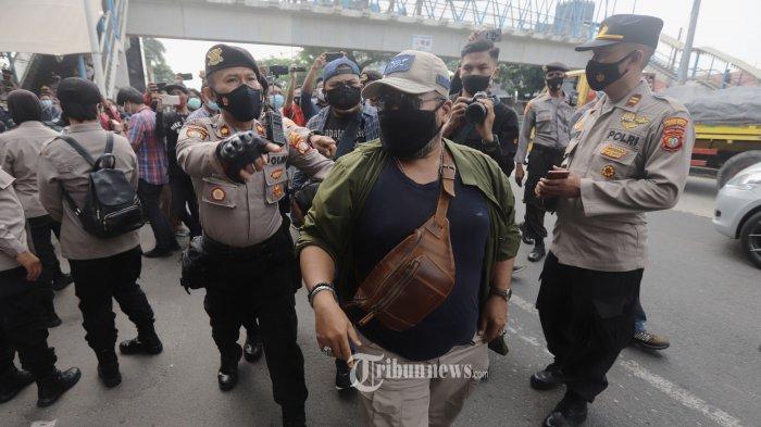 Polisi menghalau pendukung Rizieq Shihab yang akan menggelar aksi dukungan di depan gedung Pengadilan Negeri (PN) Jakarta Timur, Jumat (19/3/2021). Penjagaan ketat dilakukan terkait sidang dakwaan Rizieq Shihab atas tiga kasus yaitu kasus kerumunan di Petamburan, Jakarta Pusat, kasus kerumunan di Megamendung, Puncak, dan kasus tes usap (swab test) palsu RS Ummi Bogor. TRIBUNNEWS/HERUDIN