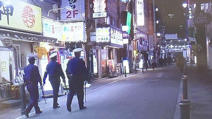 Polisi dalam satu tim termasuk polisi wanita sedang berjalan mengawasi masyarakat di Shimbashi Tokyo, Jumat (10/4/2020) malam.