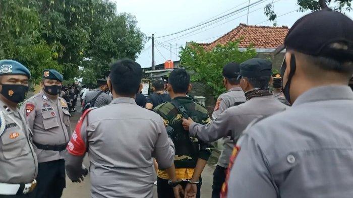 Polisi saat mengamankan pelaku terduga yang menewaskan 2 petani tebu warga Majalengka pada lahan tebu PG Jatitujuh di Desa Amis, Kecamatan Cikedung, Kabupaten Indramayu, Senin (4/10/2021).